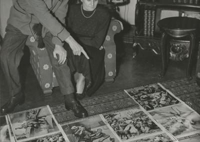 Rino Ferrari con la moglie Giulia davanti ad alcune sue illustrazioni della rivista Radar -  Parigi,  1950