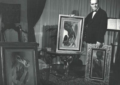 Rino Ferrari nella sua casa di Parigi con alcuni dei suoi quadri a olio.